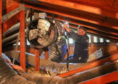 Photo of mounting fan in attic.